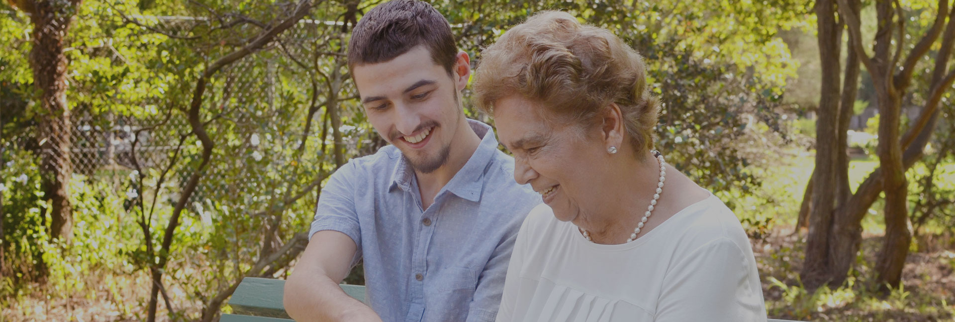 A photo of a young man and an old lady looking at IPad