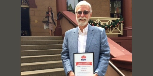 Photo of a old man holding a certificate